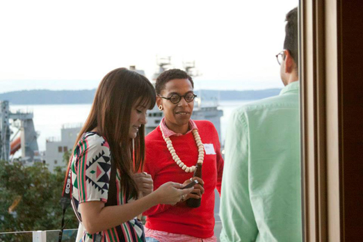 Elaine McMillion and Lyric R. Cabral. Foreground, Nandan Rao's back; background, a huge battleship on the Puget Sound.